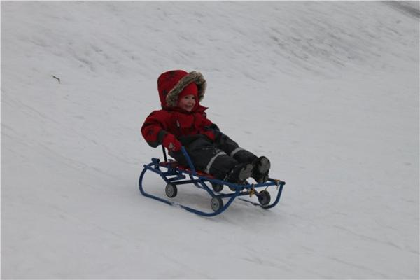 ребёнок катается на санках-коляске