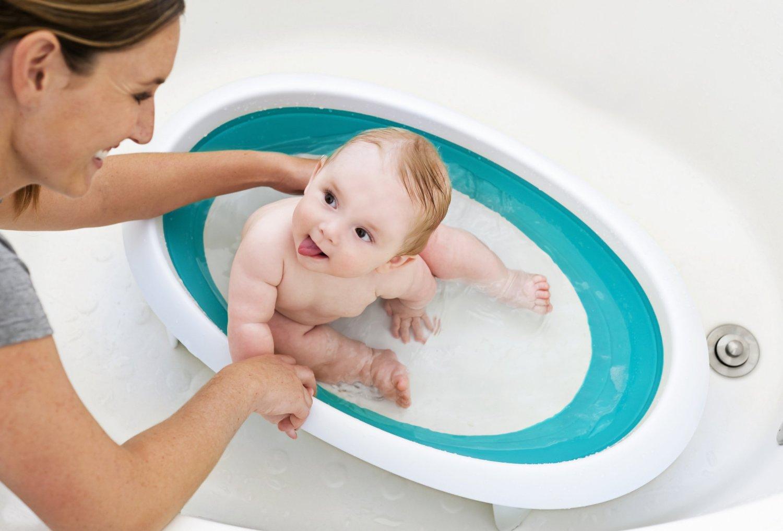малыша купают в детской ванночке