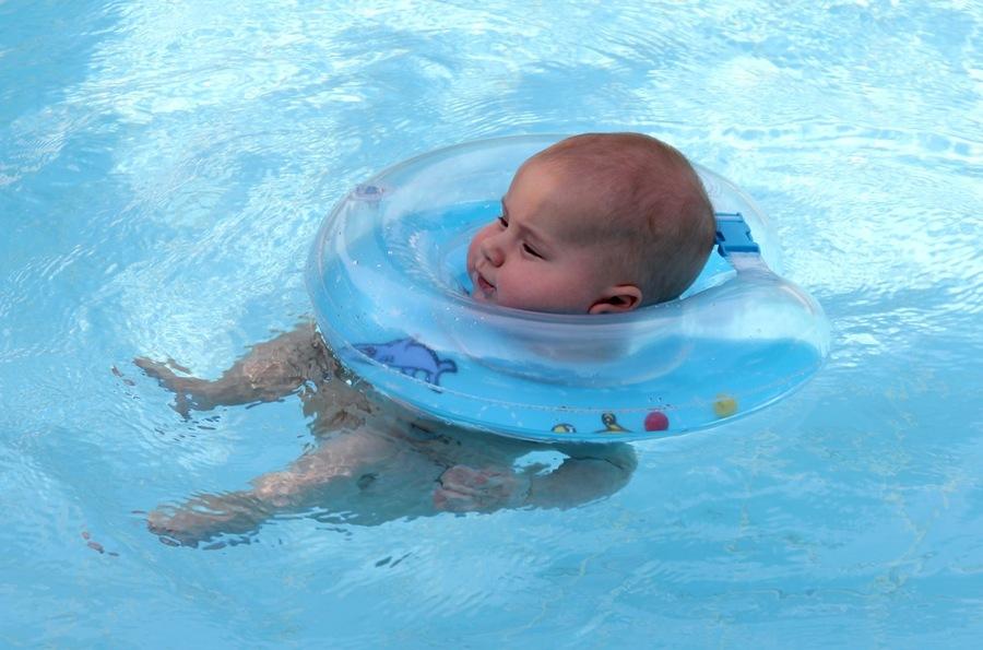 ребёнок плавает в круге для купания новорожденных