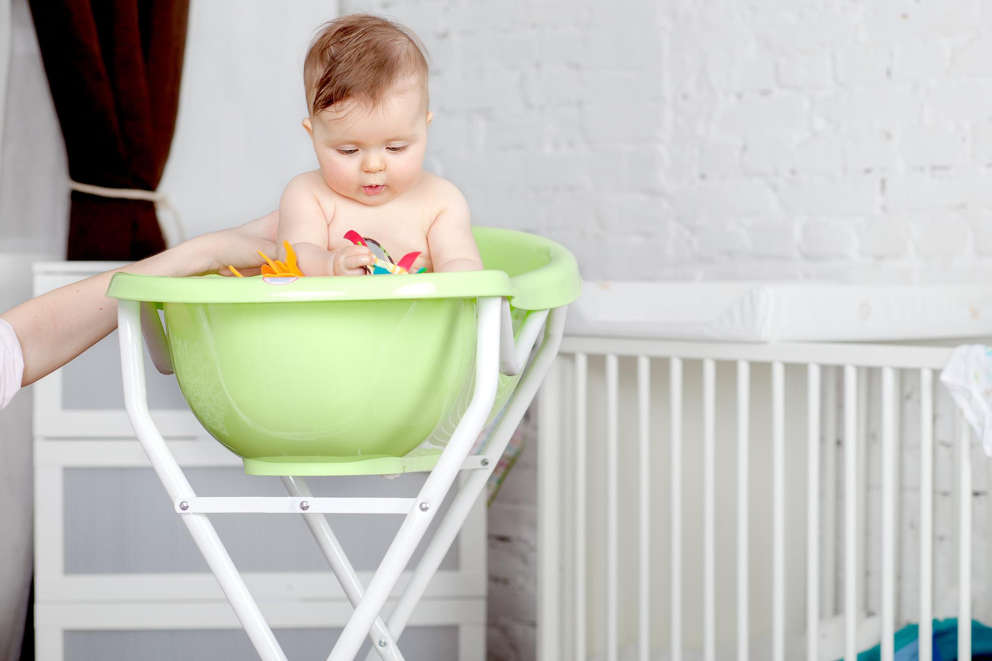 малыш в ванночке для новорождённых на подставке